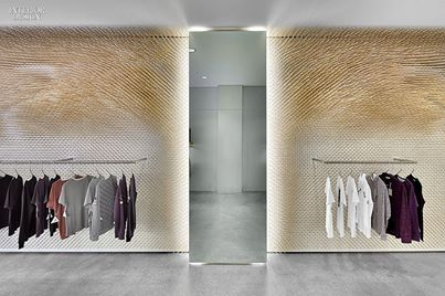 Fluorescent tubes backlight the sole mirror at Mrqt luxury boutique in Stuttgart, designed by ROK