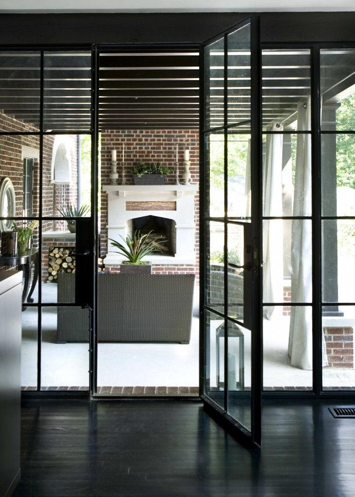 dramatic black steel framed windows and doors leading to a covered patio