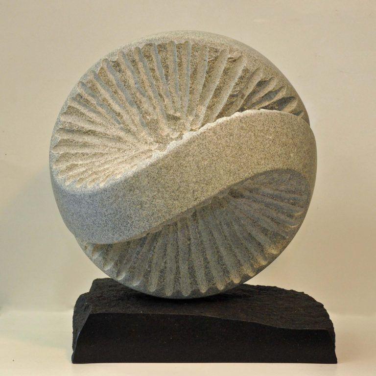 Livshjul. Lys granit på sokkel af diabas. 62 cm.