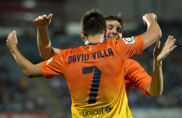 Barcelona's Argentinian forward Lionel Messi (R) celebrates with Barcelona's forward David Villa (L) after scoring during the Spanish league football match Getafe vs Barcelona at the Alfonso Perez stadium in Getafe near Madrid on September 15, 2012