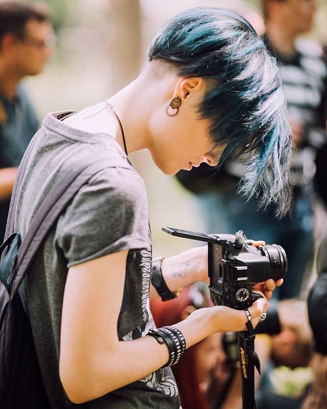 Leather bracelet, T-shirt, blue hair.