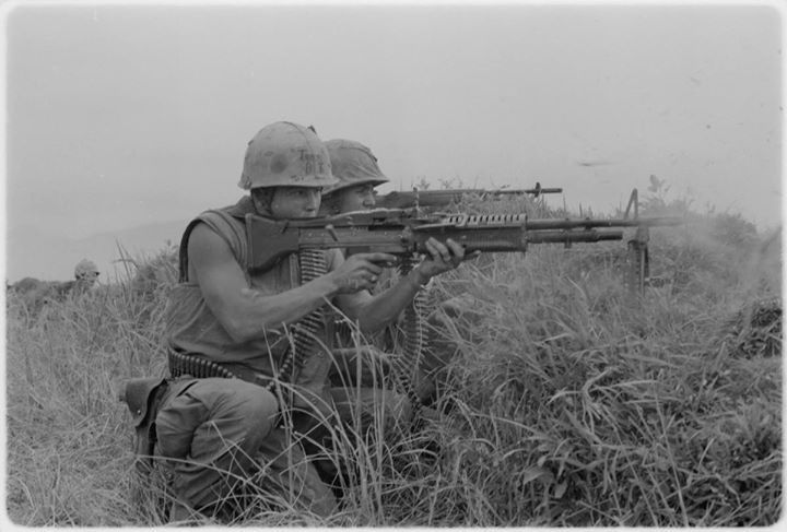 A machine gunner and a rifleman from the 5th Marine Regiment fire at
