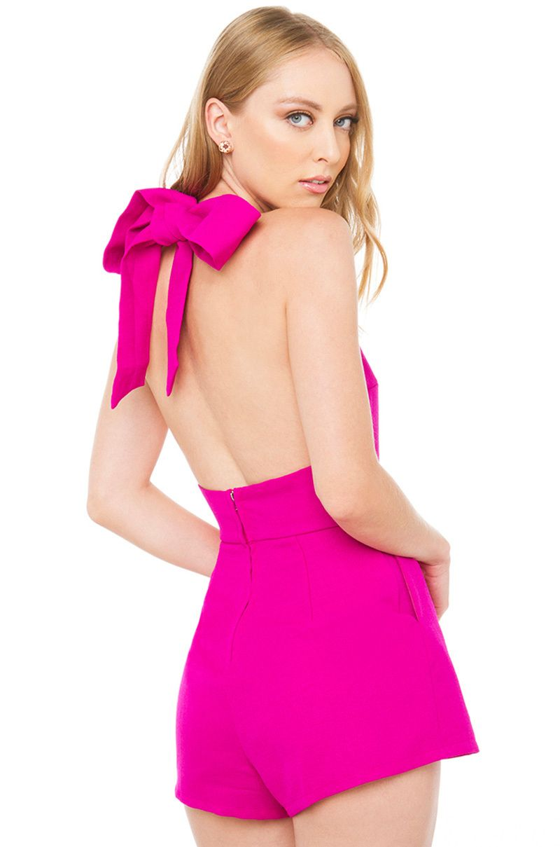 Estelle Magenta Bow Romper features a high neck, self-tie halter top, open back, pockets, and an exposed back zipper closure. Free standard U.S. shipping $75+.