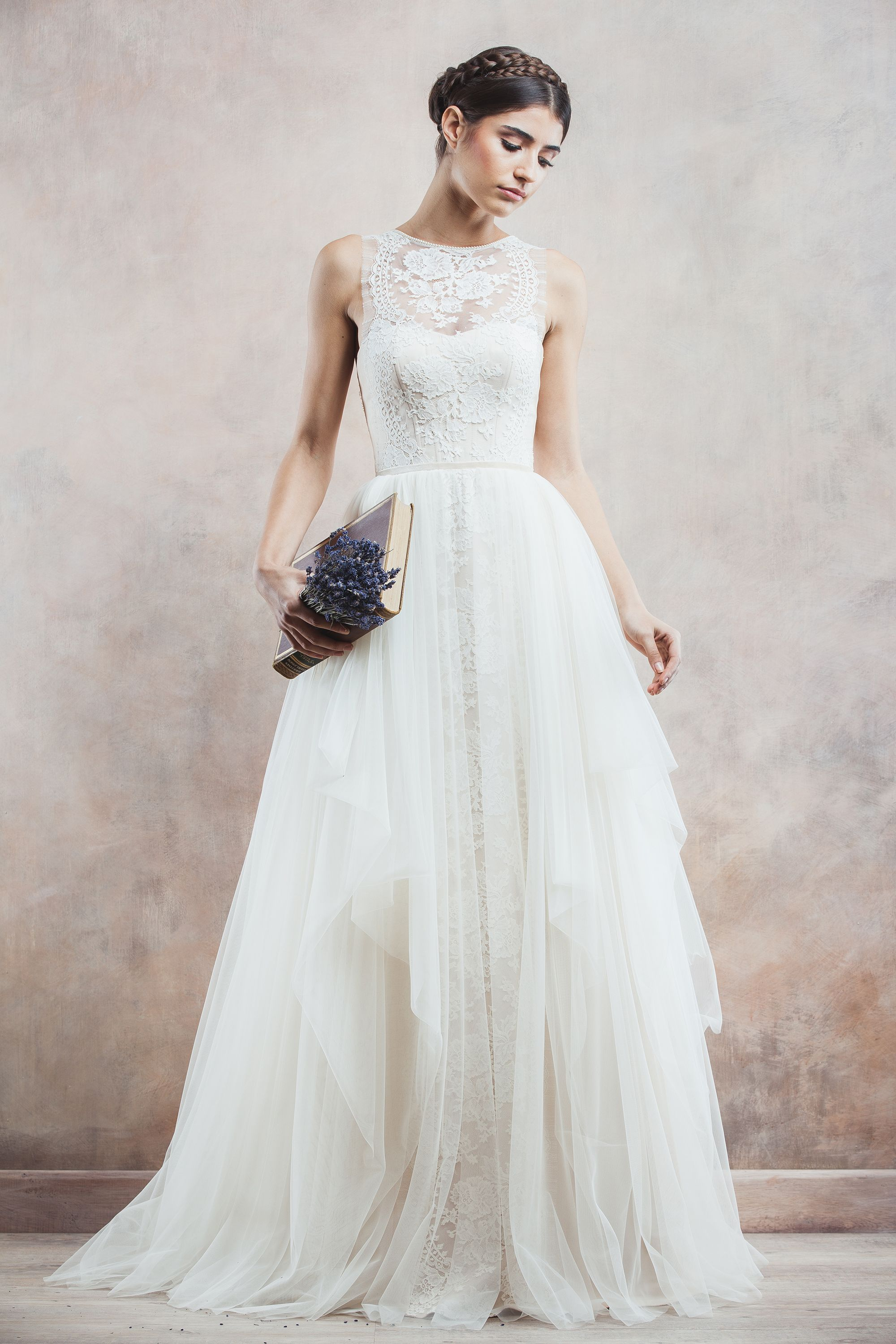 Looks like coming out of Russian literature, innocent and delicate, of pure femininity, iconic, the Anisia wedding gown is a love poem. The lace which makes us think of the dowry of an aristocratic grandma, delicately edged by Swarowski pearls, wavy tulle and the lavender bouquet, all enhance mystery and define the atmosphere of your own love poem.
