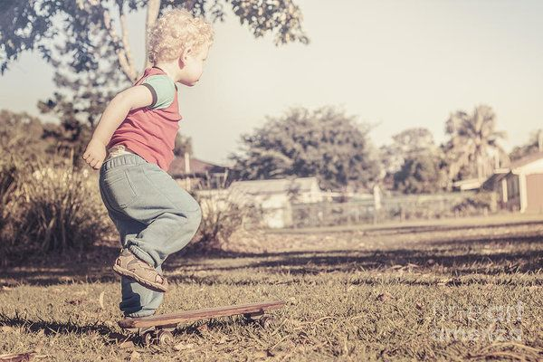 Authentic faded brown vintage image of an adorable three year old child determined to skateboard on a wooden 1950s deck on grass field surface. Trial run by Ryan Jorgensen