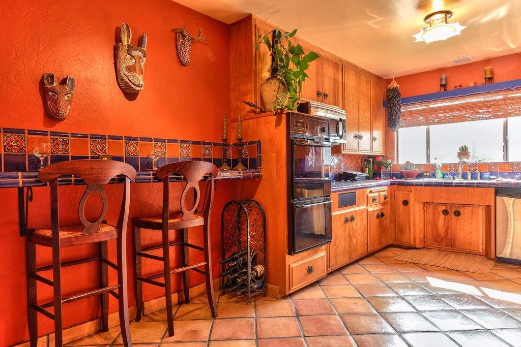 The rust and blue in this kitchen is so warm and energizing! Love ...