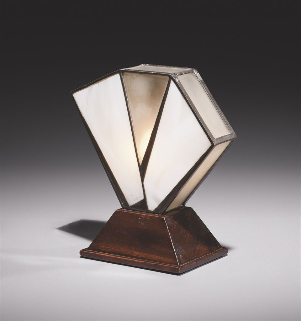 Jean Perzel (1892-1986) Lampe à poser, vers 1925 De forme hexagonale, la monture en plomb, enchâssant dix plaques en verre dépoli ou pâte de verre, reposant sur une base rectangulaire à pans coupés en bois Hauteur : 27,5 cm. (10¾ in.) Signée 'J. PERZEL' sur une plaque en pâte de verre, vers la base