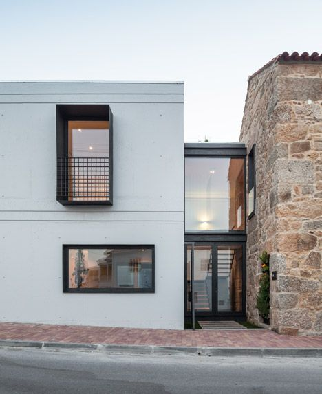 A glass-fronted stairwell joins a craggy stone Portuguese house to its new concrete extension.