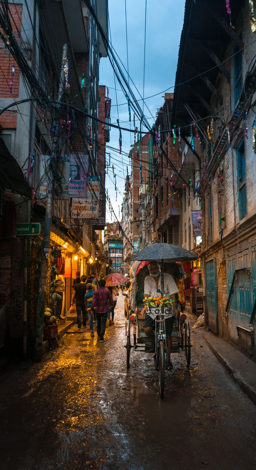 A cycle rickshaw driver pedaling along a market street on a monsoon evening in the Thamel area of Kathmandu, Nepal.