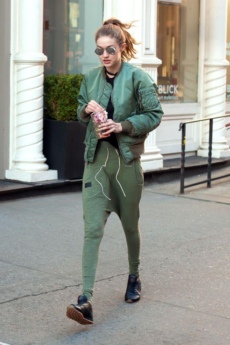 8793f4b71b831 Gigi Hadid Street Style Green Unravel Bomber Green Reebok Sweatpants Black  Reebok Sneakers Silver Linda Farrow Sunglasses
