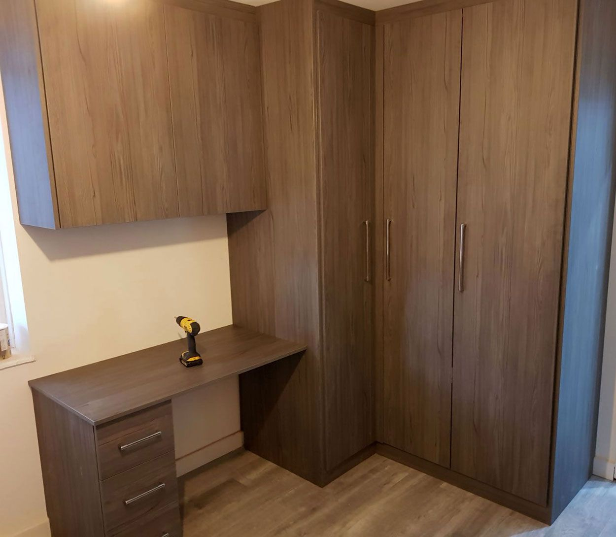 A Corner Fitted Wardrobes With Study Table In Small Bedroom By