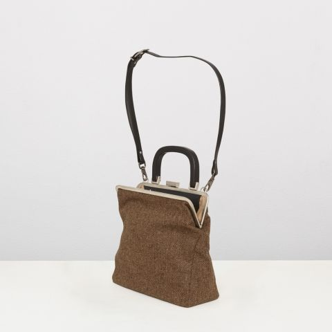 Custom made steel framed handbag with plied leather handle and detachable strap, made from undyed Manx and Hebridean wool, woven in the Outer Hebrides. Contrast cotton lining has a leather trimmed inner zip pocket. Dawn is part of the special edition Wool group, made from 100% natural wool woven in a diamond twill. Made in Hackney, UK.