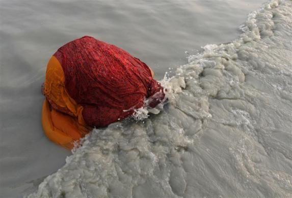 A female Hindu pilgrim takes a dip at the confluence of the Ganges river and the Bay of Bengal at Sagar Island, south of Kolkata, January 14, 2013. REUTERS-Rupak De Chowdhuri