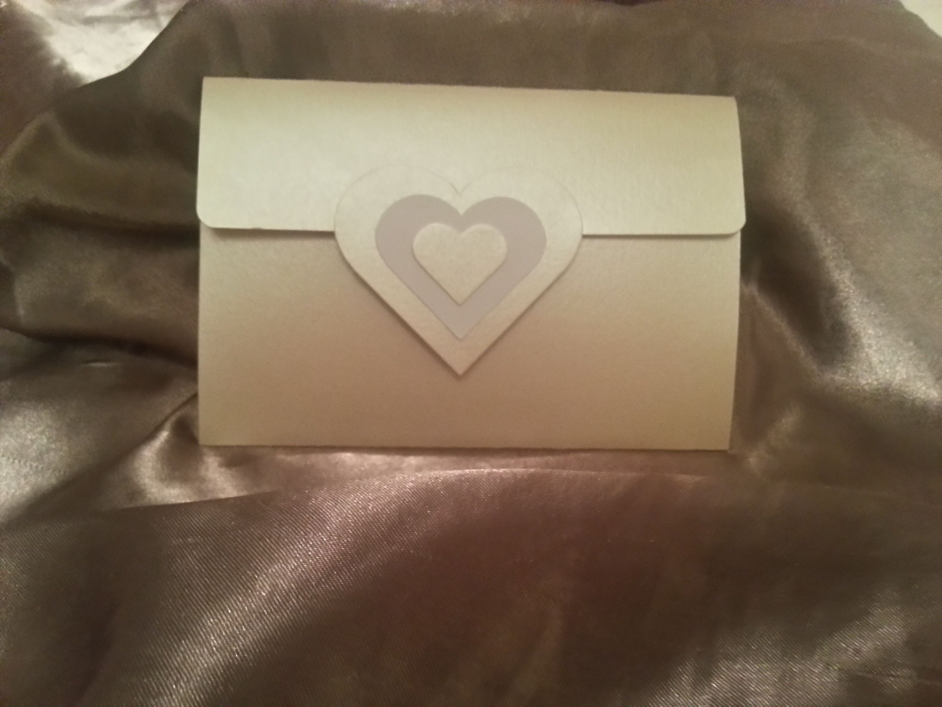 envelope shaped gold pocket fold wedding invitation with a hearts