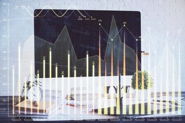 Stock market chart hologram drawn on personal computer background Multi exposure Concept of investment