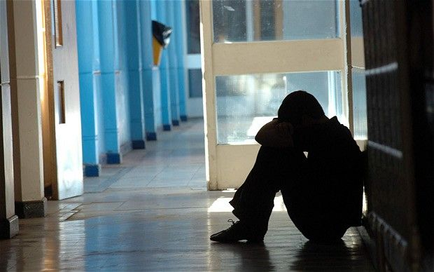 Alumno lloroso en el pasillo del colegio