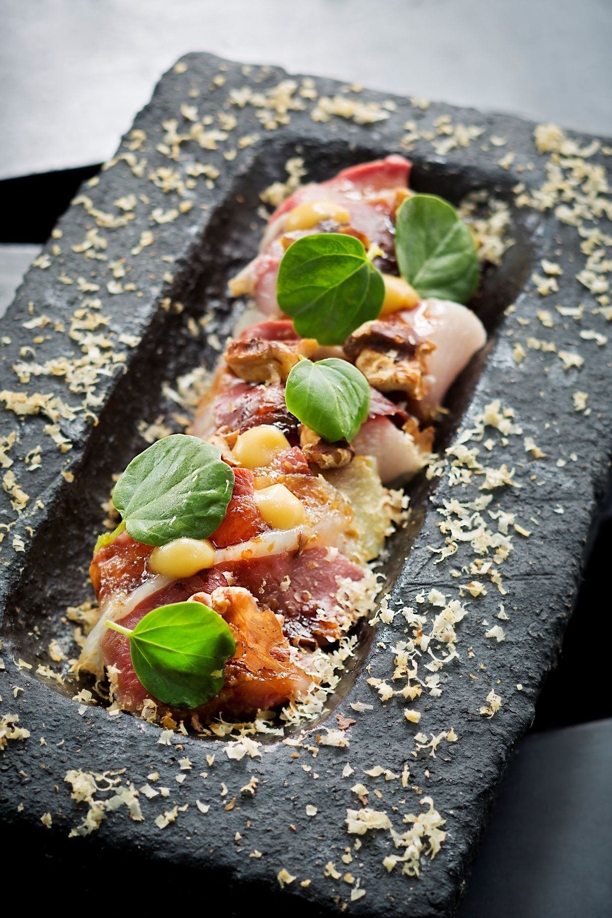 Raw hamachi with house-cured duck, shaved walnuts and soya caramel.