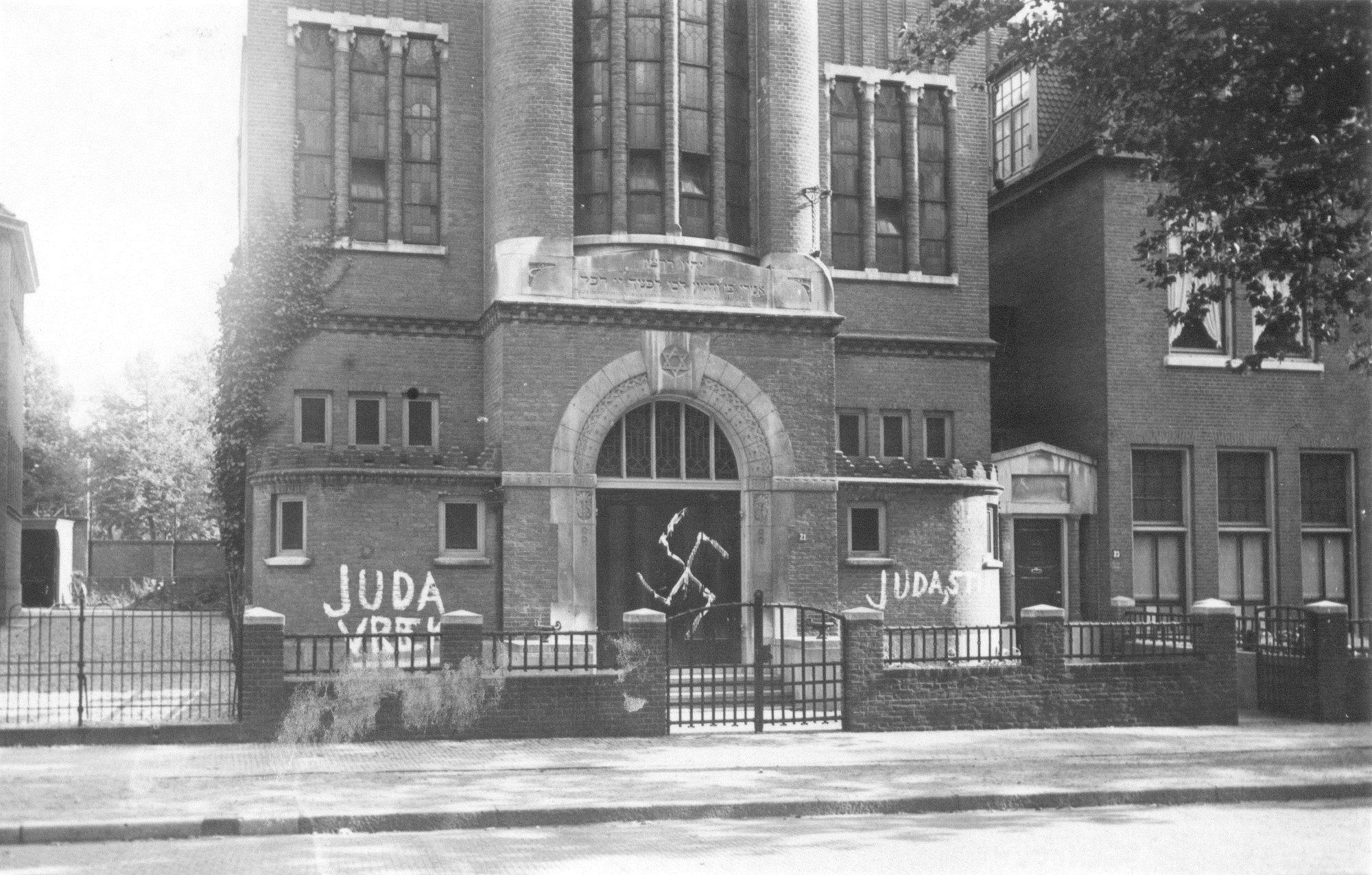 De Tweede Wereldoorlog had grote gevolgen voor de Nijmeegse joden. Dat kun je onder andere zien aan deze met hakenkruisen besmeurde Joodse Synagoge ten tijde van de Duitse bezetting. De muren van de synagoge aan de Gerard Noodtstraat werden beklad met een vlekkerig hakenkruis en teksten als 'Judas vrek' en 'Judas stik'. Dit zijn uitingen van antisemitisme in Nijmegen in 1942.