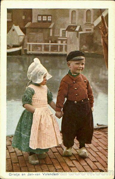Grietje en Jan van Volendam, 1940-1946 Twee kinderen poseren in dracht. Op de achtergrond het Braakje en het Doolhof, waar een aantal kippenhokken staan. Het meisje draagt een jurkje met daarover het 'lijfbontje' (soort schortje). Deze combinatie word gedragen tot het vierde levensjaar. - #Netherlands #travel