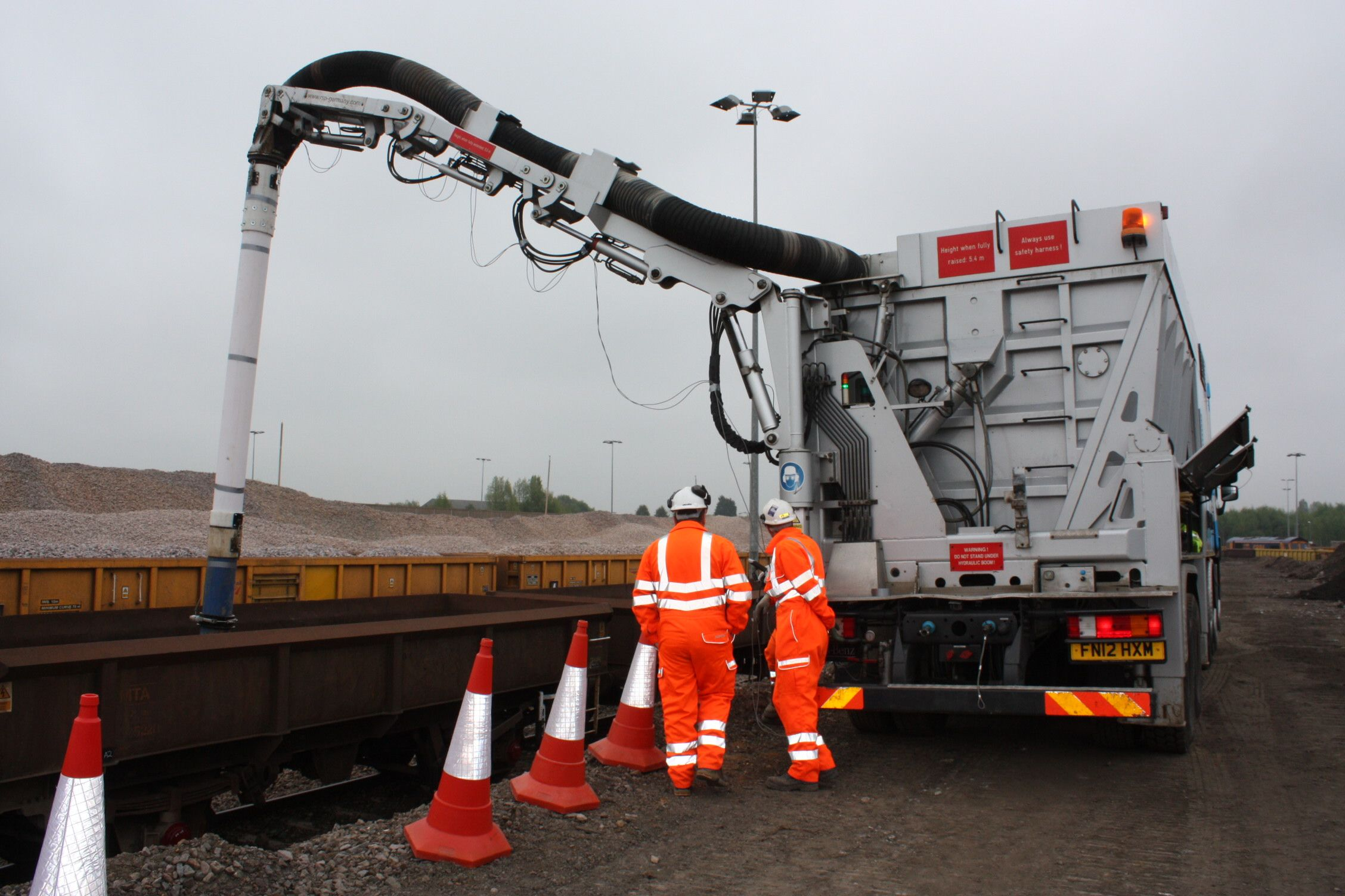 Removing rail ballast from wagons using suction excavation