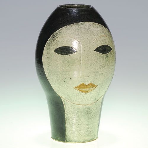 """Two-sided head vase by Susan and Theo Harlander (b. Germany, died Canada), each side depicting a starkly defined woman's face, outlined by incising and done in colored slips. Incised on the bottom """"T + S Harlander, Brooklyn, Ontario"""" w/monogram. Height 9""""."""
