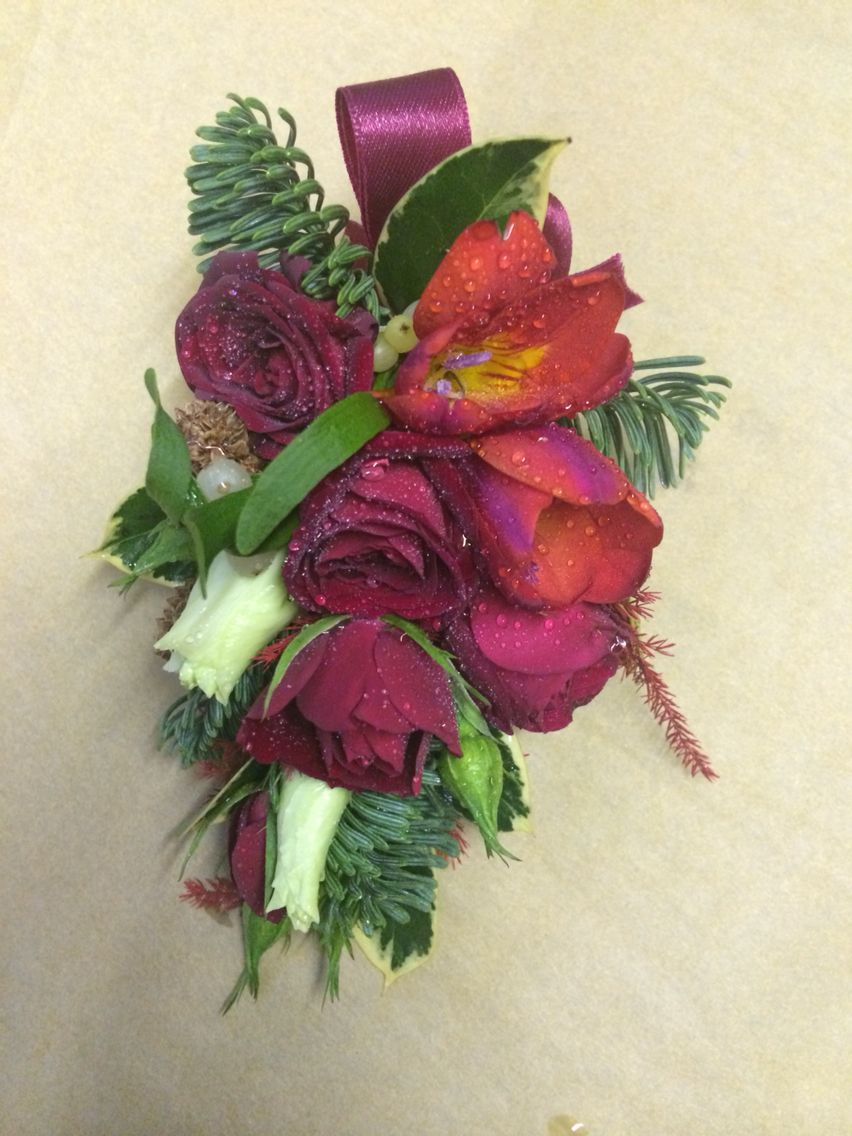 Ladies corsage- red rose, freesia , Lisianthus, with Christmas foliage #christmaswedding #pennyjohnsonflowers