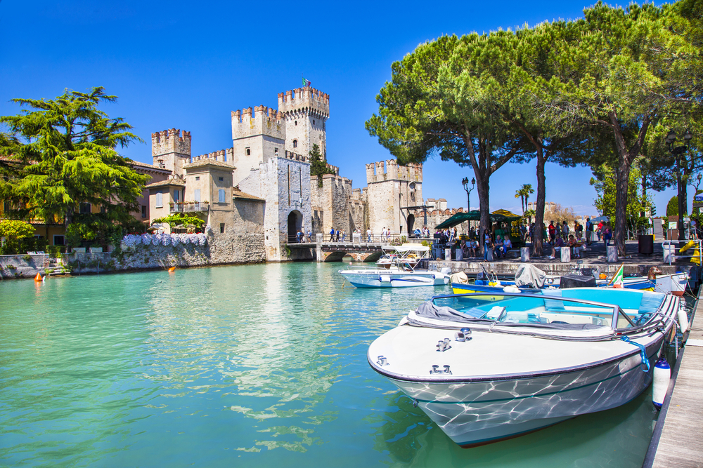7 Great European lakeside holidays for 2019 ~ The Crazy Travel Trip    The Spiaggia Giamaica, also called Jamaica beach resides at the end of Sirmione peninsula and spreads out to the southern shore of Lake Garda. Though the beach isn't very popular, but the experience will definitely be worth it. A white smooth rock forms a large slap on the beach. There's a gorgeous mountain view at one side of the beach and the view of the old village of Sirmione on the other side.
