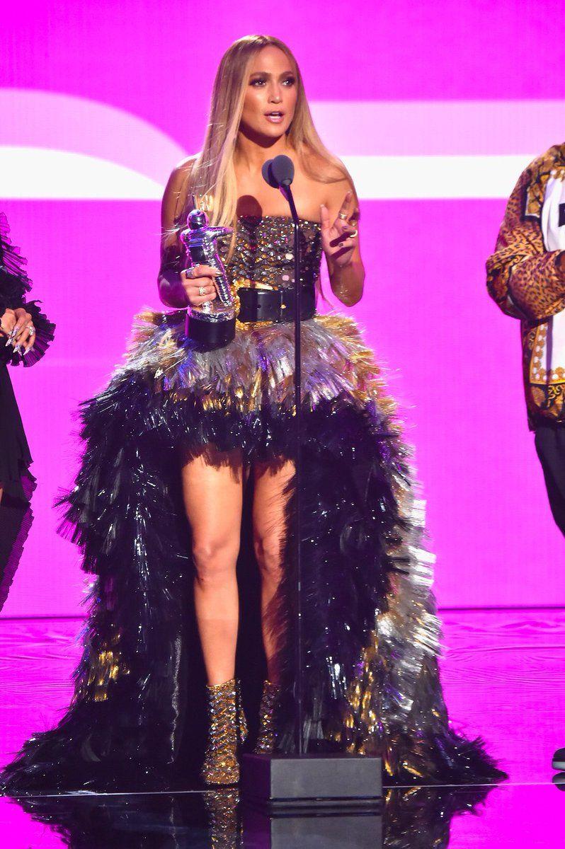 Jennifer Lopez en robe courte devant longue derrière bouffante bustier droit et bottines doré