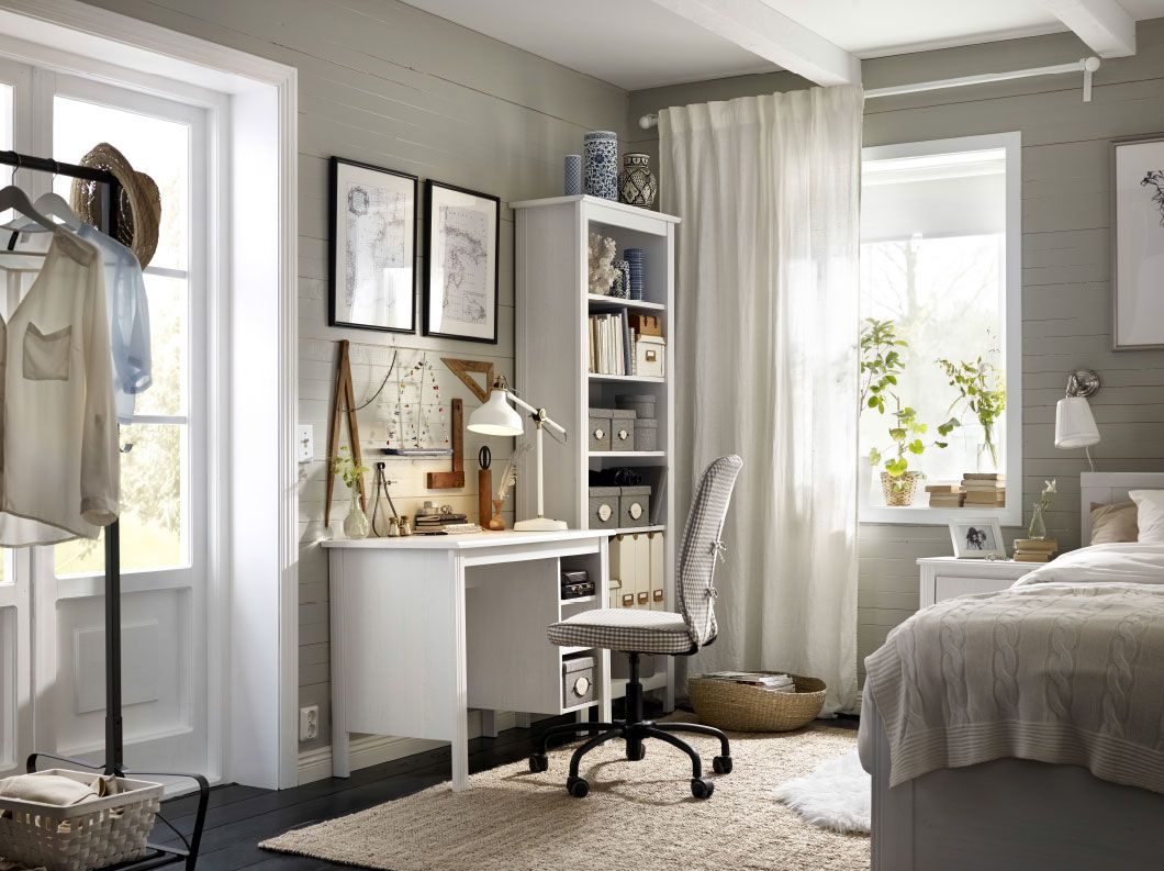 A corner in the bedroom with a white desk and a high bookcase ...