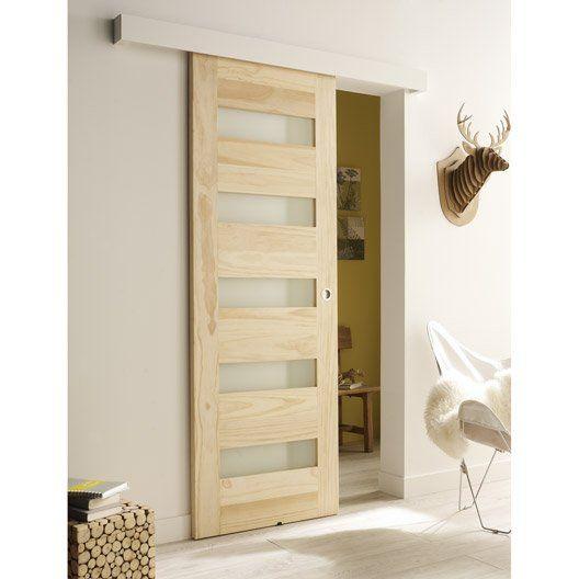 Une porte coulissante avec rail haut visible Cette porte en bois