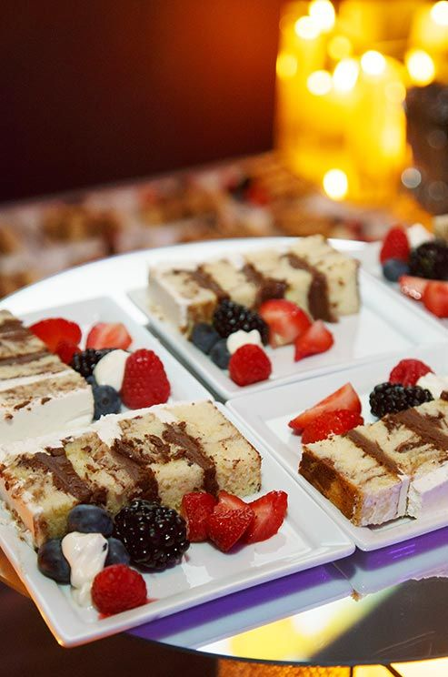 Slices of vanilla cake with chocolate filling are served with fresh berries and cream.