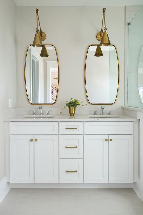 Two Antique Brass Swing Arm Pendants Illuminate Two Brass Mirrors Placed  Over A White Dual