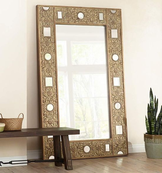 Large Gold Floor Mirror Leaning Against Wall With Bench And Aloe