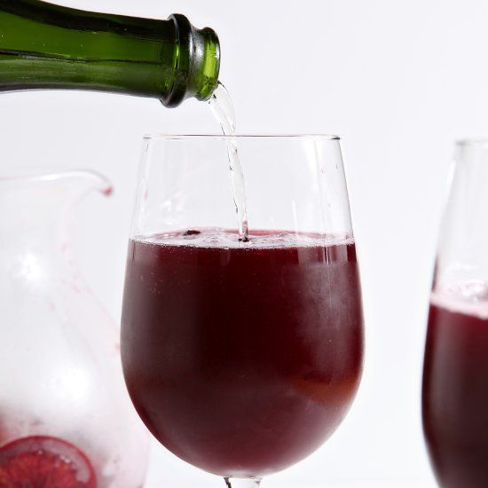 Winter sangria, chock full of orange and cranberry goodness, is combined with a favorite bottle of bubbly to create this cocktail.