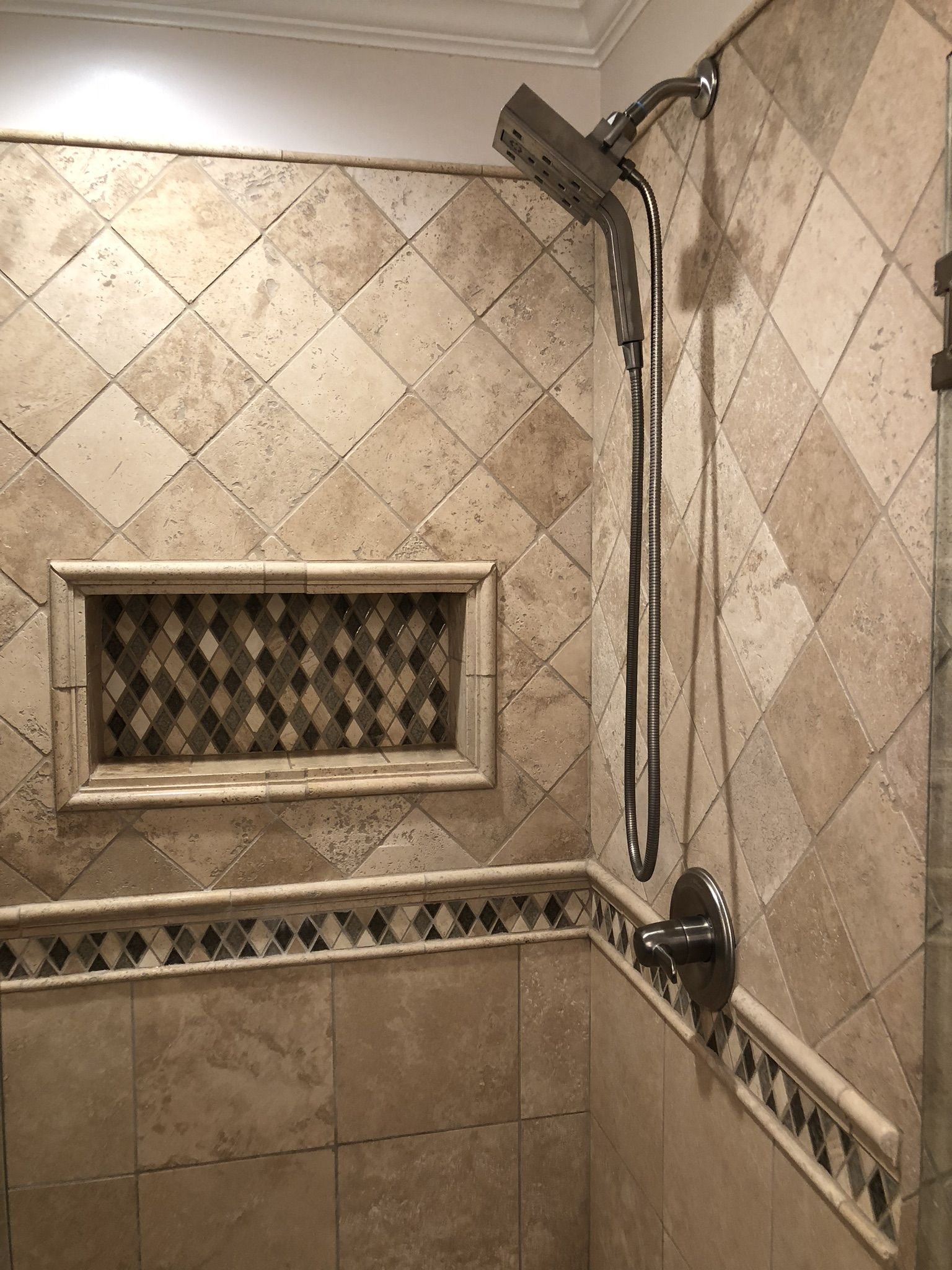 Tile shower with mosaic band and larger niche Flooring