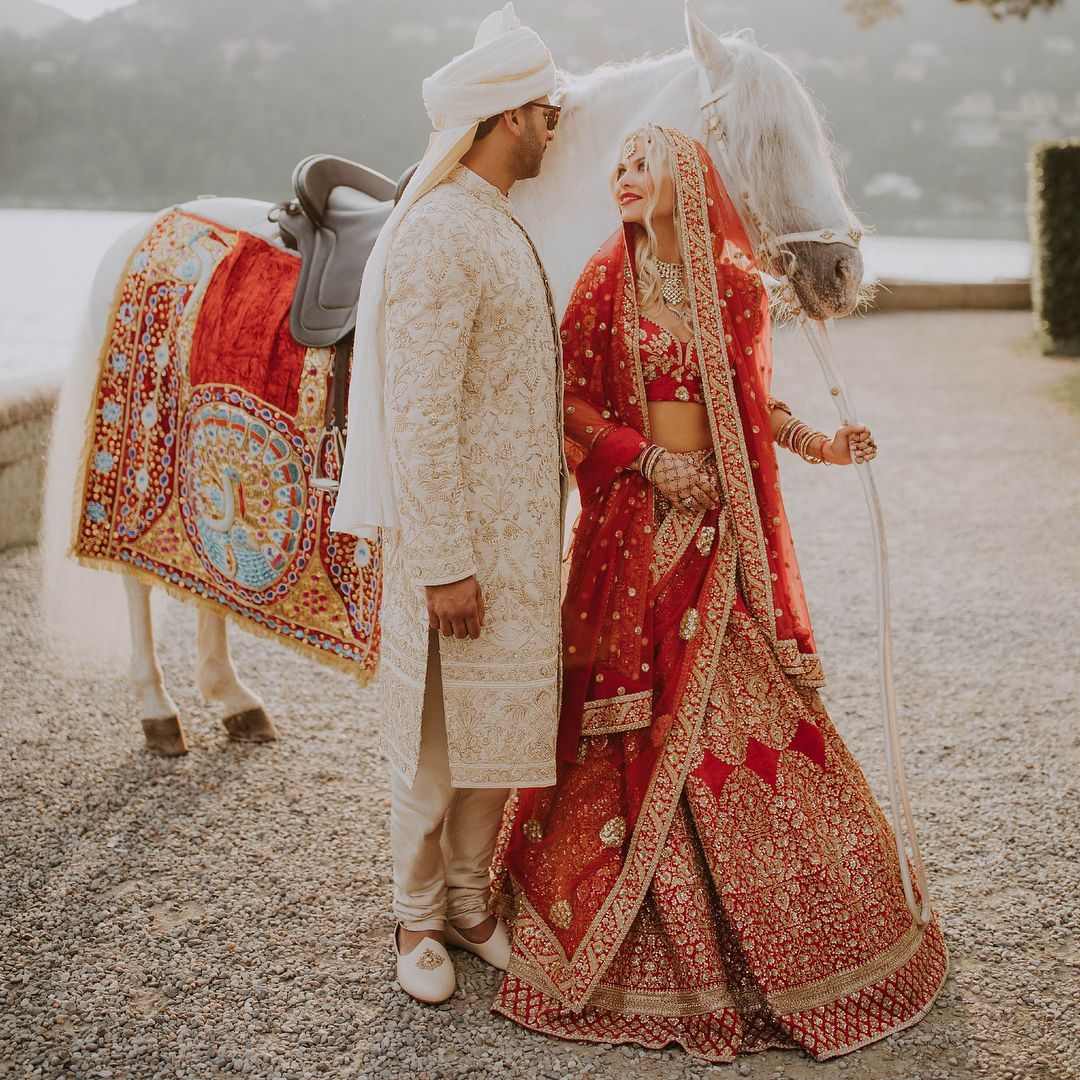 Brides In Red And Grooms In Ivory Are A Quintessential Image Of North Indian Weddings Real Bride Indian Wedding Outfits Bridal Lehenga Red Party Dress Classy