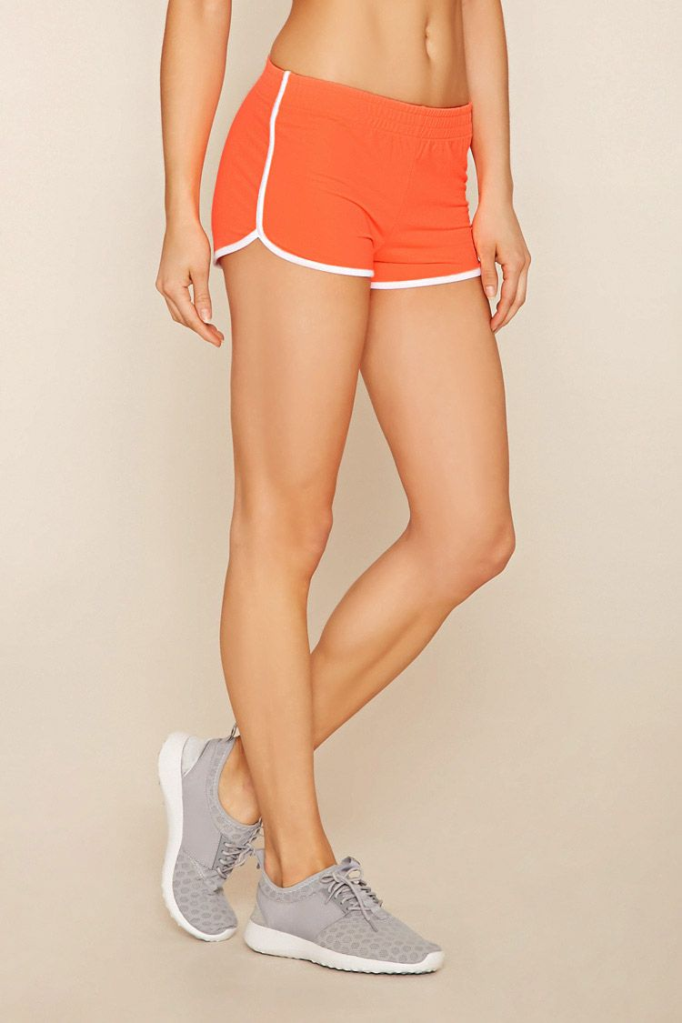 A pair of knit athletic shorts with an elasticized waist, contrast trim, and a dolphin hem.