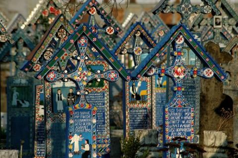 Merry Cemetery -Sapantza Romania.  Its tombs are decorated with bright naïve paintings and epitaphs that describe in a poetical way the life of the dead person. There are around 800 wooden crosses, mostly decorated by local artist Stan Ioan Patras, who also rests in this incredible cemetery.