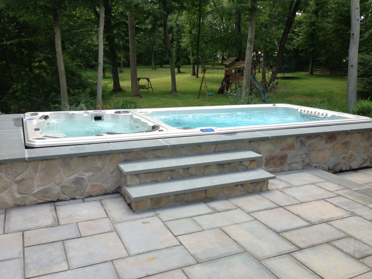 Hydropool Dual Temperature Swim Spa Installed In A Stone Enclosure Learn More About Hydropool Self Cleaning Swi Hot Tub Swim Spa Swim Spa Swim Spa Landscaping
