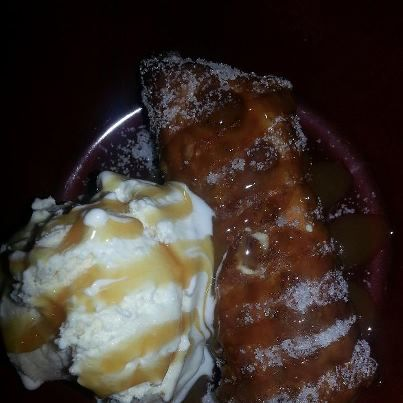 Fried Elvis Eggroll, Banana Chocolate chips and peanut butter wrapped in an eggroll wrapper and fried crispy then tossed in sugar and topped with a scoop of homemade vanilla icecream and caramel sauce