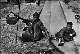 Henri Cartier-Bresson 1949 CHINA. Zhejiang. Hangzhou. 1949. A child retained by a cord, his blind father carrying the baby and a basket for contributions, a sad but not uncommon sight on Hangzhou streets in the last chaotic days of the Kuomintang regime.