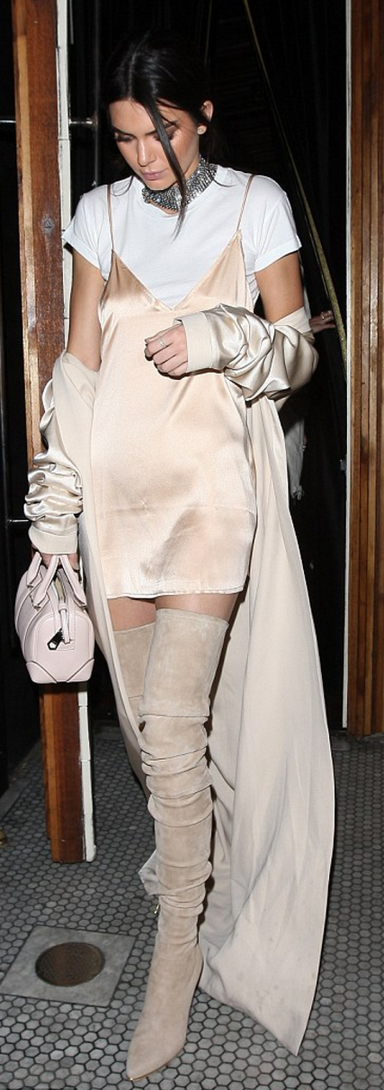 c610def6a64e7 Who made Kendall Jenner's silver jewelry, tan thigh high boots, satin nude  trench coat, and beige handbag?