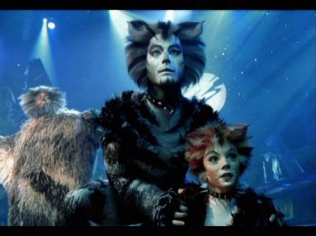 Rumpleteazer with Rum Tum Tugger in background Cats The Musical - best of lyrics invitation to the jellicle ball