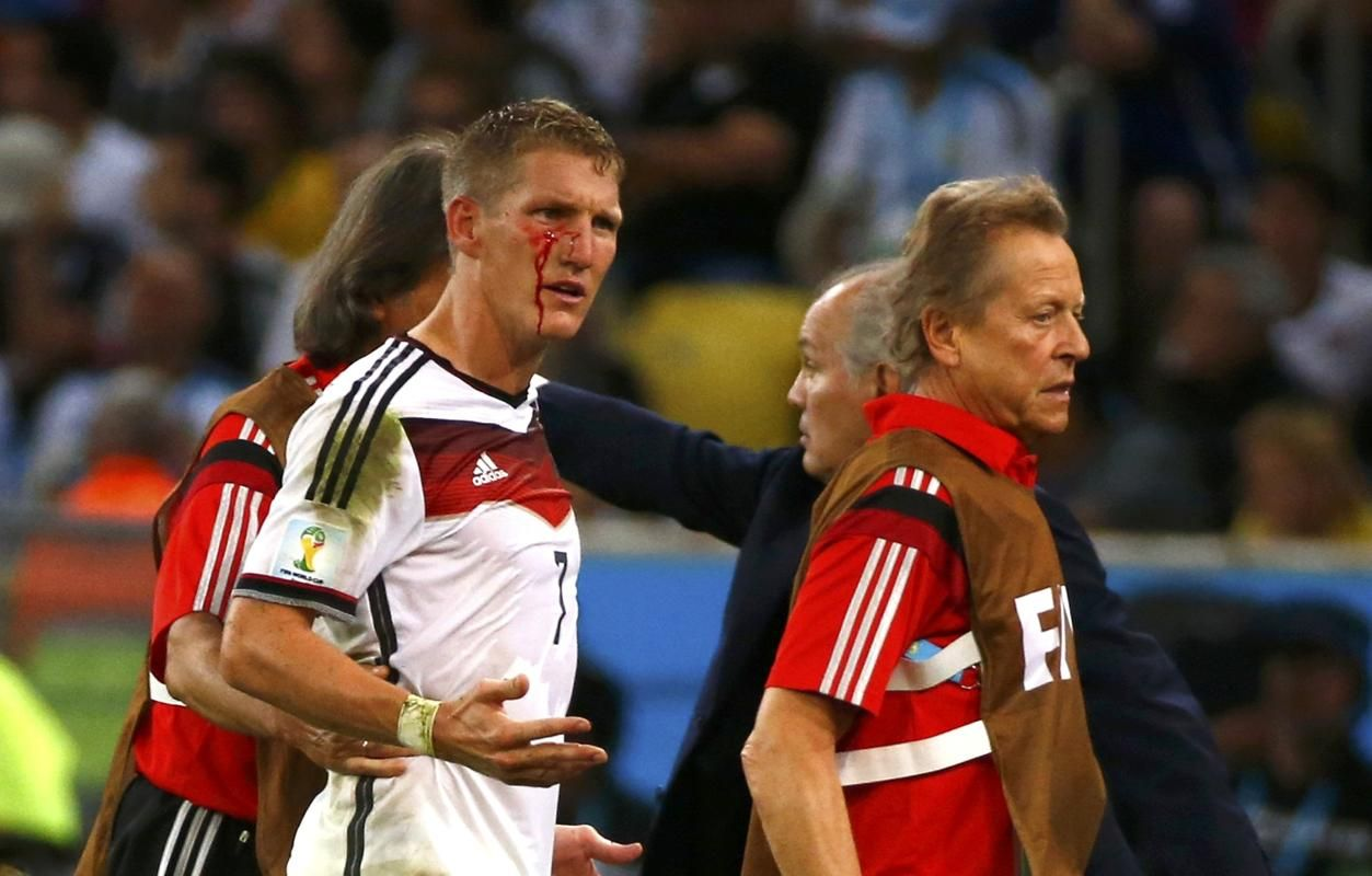 Germany's Bastian Schweinsteiger is led off the pitch while bleeding during extra time in the 2014 World Cup final between Germany and Argentina at the Maracana stadium in Rio de Janeiro July 13, 2014.
