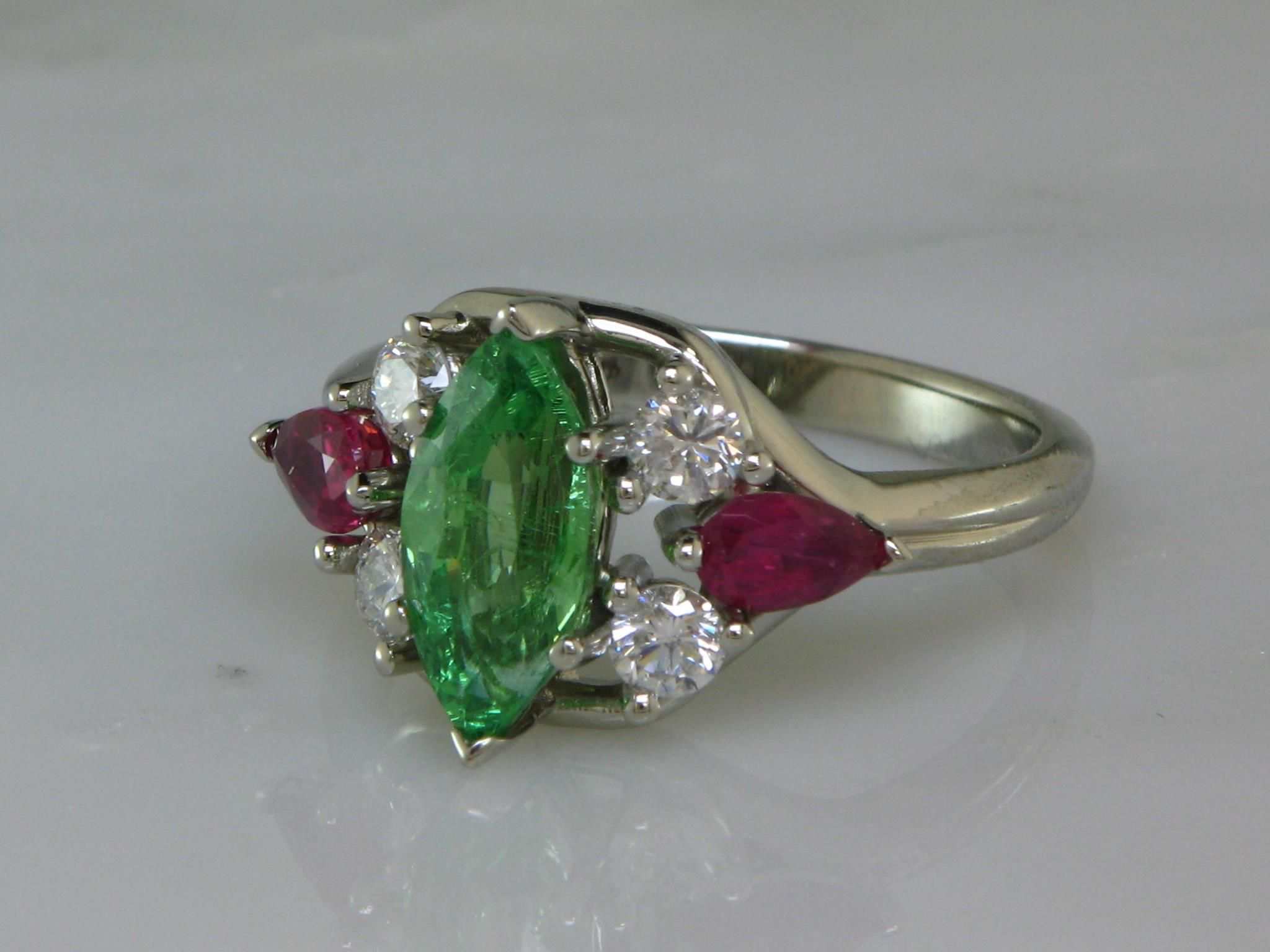 Tsavorite Garnet, a variety of Demantoid Garnet demonstrates the wide variety of colors in the spectrum that Garnet posesses. The Vibrant emerald green variety of garnet, Tsavorite graces the center of this ring. A marquise shape Tsavorite is flanked by four diamonds and two matched pear shape rubies in 14K White Gold and a euroshank to prevent rolling on the finger. The Center Tsavorite weighs 1.82 carats, the Rubies total  .66 carats and the Diamonds total .40 carats total weight…