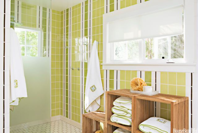 """Ann Sacks tiles stripe a California pool bath from floor to ceiling, giving the space a modern, unified look. To avoid breaking up the continuity, designers Heidi Bonesteel and Michele Trout frosted the shower wall only in the middle. """"We love stripes, but we'd never seen them before in a wall tile. It's perky and different,"""" Bonesteel says. Ann Sacks Capri ceramic floor tiles. Dornbracht hooks."""