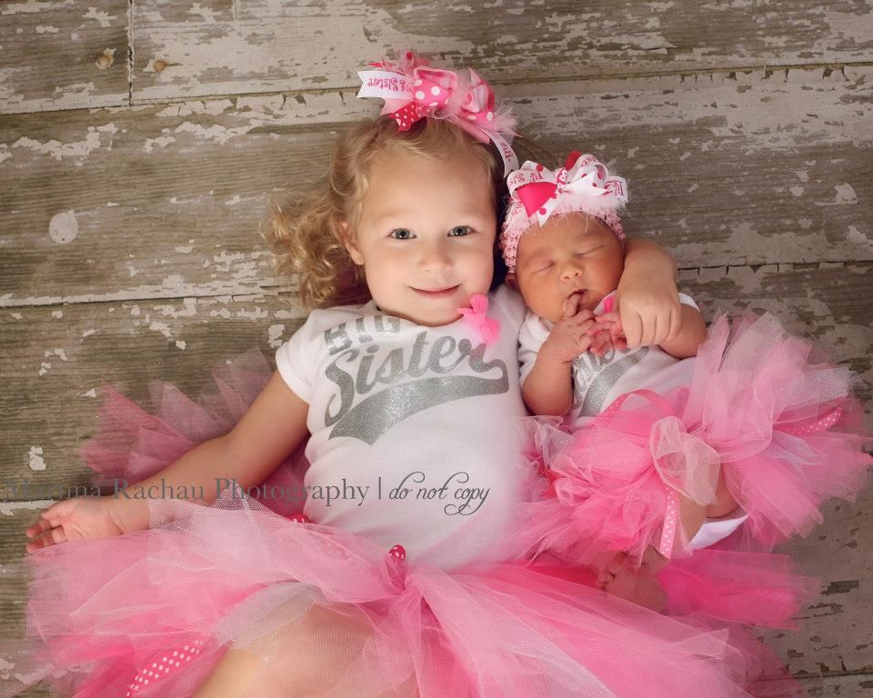 Newborn baby and big sister in pink