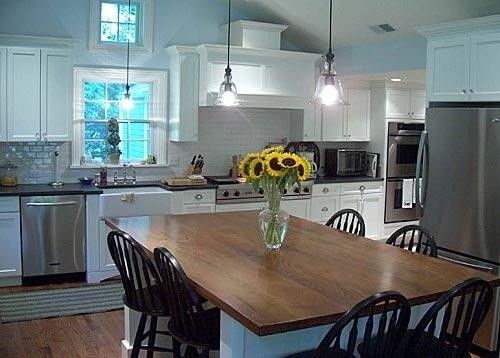 Love this gorgeous kitchen! I love how it has white cabinets with stainless steel appliances and the eat-int style table with a farm table wood table top & black chairs! Proves that you can mix black & brown!    #kitchens