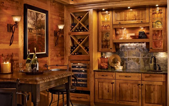 Rustic kitchen cabinets by KraftMaid  With stacked bottle storage and framed wine cooler in a