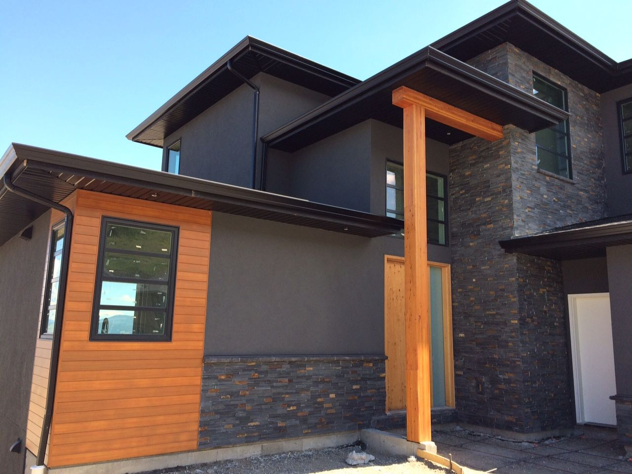 Modern home by mdt homes kamloops bc with charcoal for Black stone house